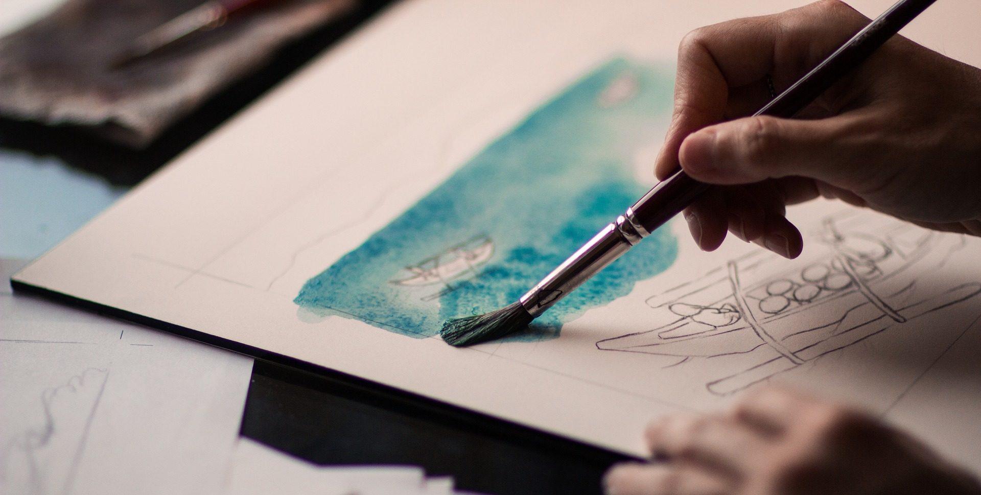 Jemand malt ein Aquarell mit Pinsel.